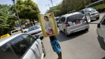 A street vender holds a calendar featuring Myanmar's opposition leader Aung San Suu Kyi in a Yangon street, Myanmar on Thursday, Nov. 12, 2015. (AP / Gemunu Amarasinghe)