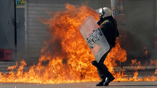 Policeman tries to avoid a petrol bomb in Athens