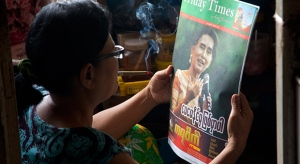 A woman reads a newspaper with Myanmar opposition leader Aung San Suu Kyi on the cover at her residence in the outskirts of Yangon, Myanmar, Thursday, Nov. 12, 2015. (AP / Khin Maung Win)