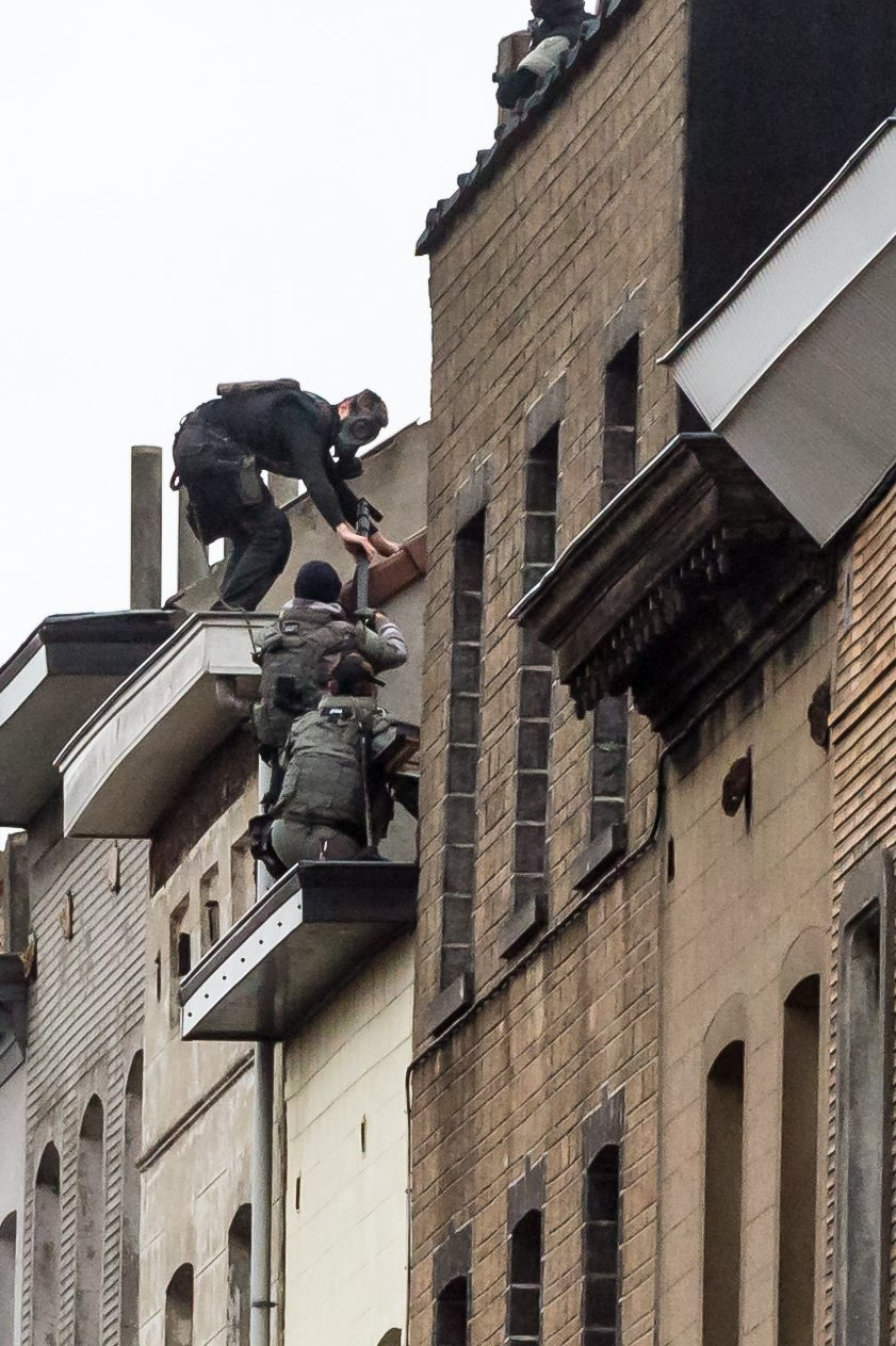 Special intervention forces climb on top of a roof as they prepare to enter a house in Brussels on Monday, Nov. 16, 2015. (AP / Geert Vanden Wijngaert)