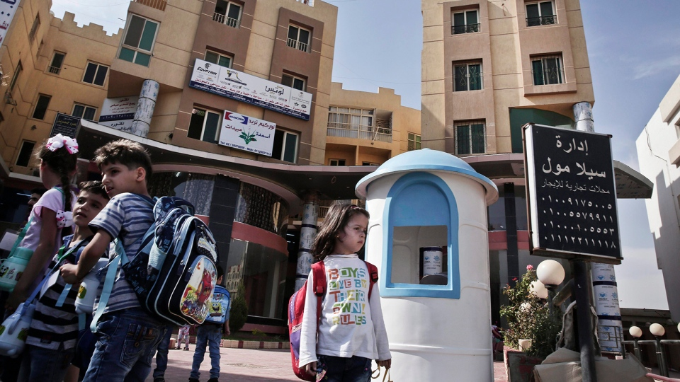 In this Monday, Oct. 12, 2015 photo, Syrian refugee students wait for their buses and families to pick them up after school, at the Civilization Builders Educational Center, background, in the 6th of October suburb west of Cairo. (AP / Nariman El-Mofty)