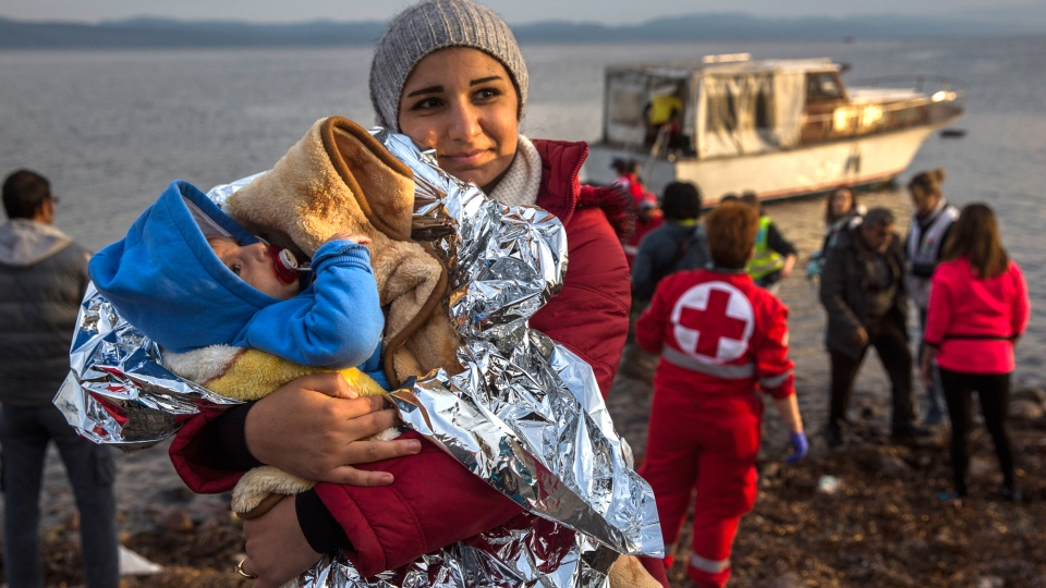 A Syrian woman holds her baby after their arrival on a small boat from the Turkish coast on the northeastern Greek island of Lesbos, Monday, Nov. 16, 2015. (AP / Santi Palacios)