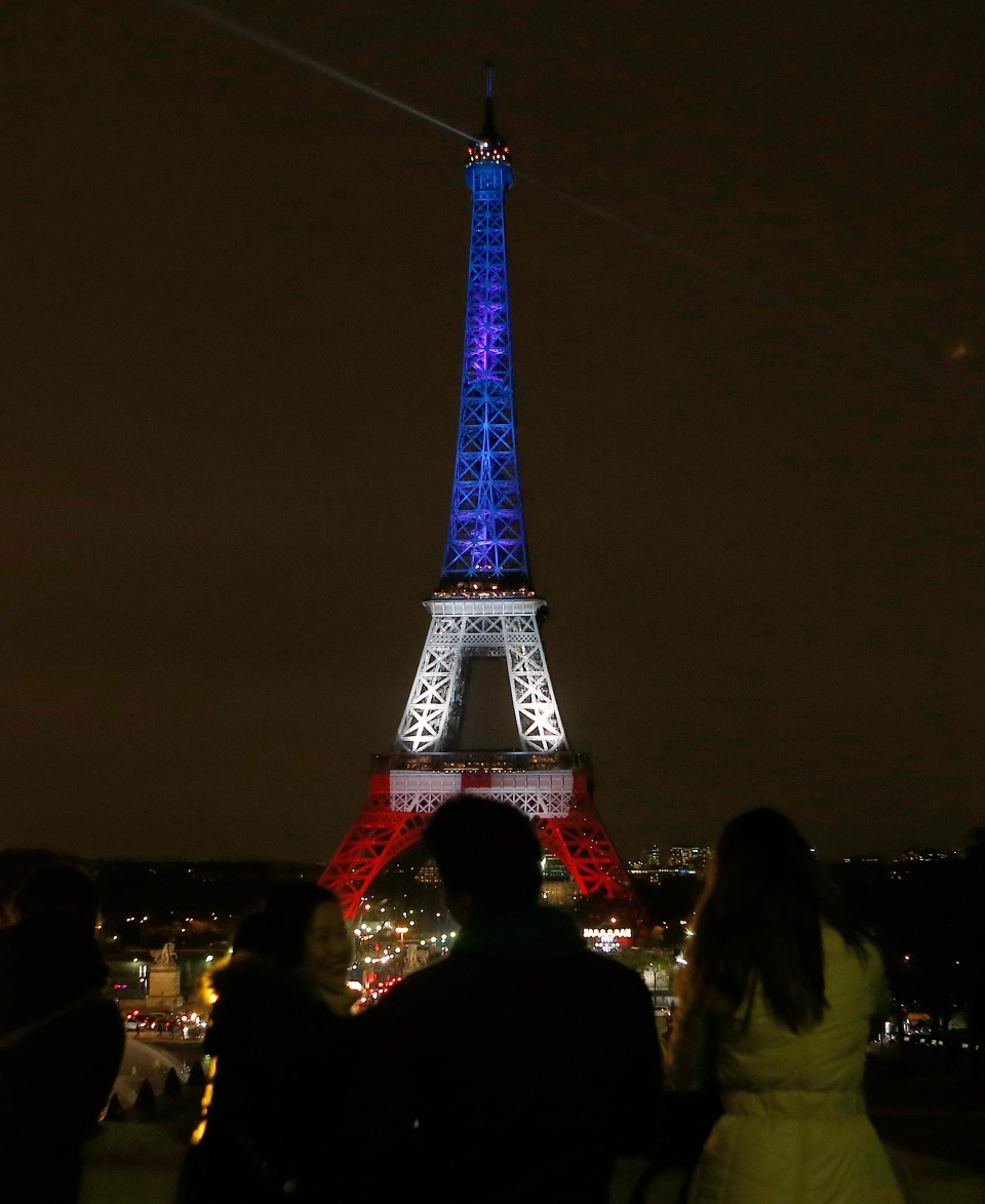 People watch the illuminated Eiffel Tower in the French national colours red, white and blue in honour of the victims of the terrorist attacks last Friday in Paris, Monday, Nov. 16, 2015. (AP / Frank Augstein)