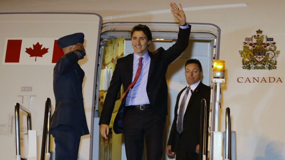 Prime Minister Justin Trudeau waves as he disembarks from his plane as he arrives for the Asia-Pacific Economic Cooperation (APEC) summit in Manila, Philippines on Tuesday, Nov. 17, 2015. (AP / Aaron Favila)