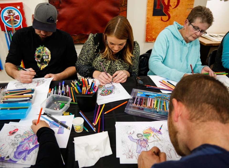 Adults colour in designs by Crystal Salamon, an illustrator and adult colouring book designer, at a colouring event at a gallery in Black Diamond, Alta., Monday, Nov. 16, 2015. (THE CANADIAN PRESS/Jeff McIntosh)