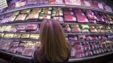 Woman standing in front of meat counter in superma