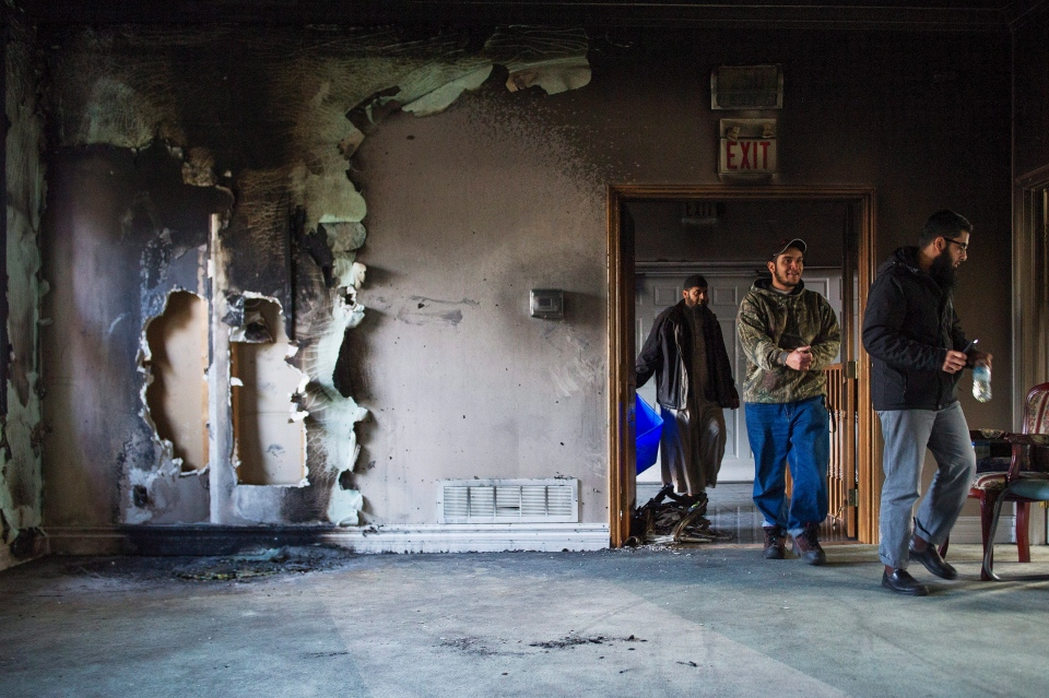 Congregation members clean up debris, on Sunday, November 15, 2015, after the only mosque in Peterborough, Ont., was deliberately set alight Saturday night. (Christopher Katsarov/THE CANADIAN PRESS)