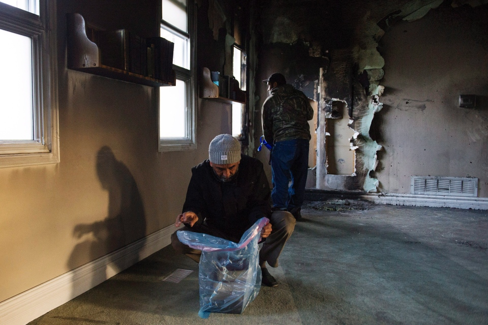 The Qur'an and other books are removed from shelves as congregation members clean up debris, on Sunday, Nov. 15, 2015, after the only mosque in Peterborough, Ont., was deliberately set alight Saturday night. (Christopher Katsarov / THE CANADIAN PRESS)