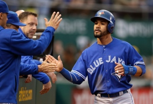 Toronto Blue Jays' Devon Travis, right, is congratulated after scoring against the Oakland Athletics in the third inning of a baseball game on July 22, 2015, in Oakland, Calif. (Ben Margot / AP Photo)