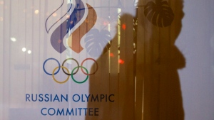 A man walking past the Russian Olympic Committee building, casts a shadow on a window in Moscow, Russia, Wednesday, Nov. 18, 2015. (AP Photo/Pavel Golovkin)