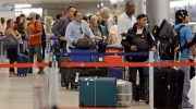 In this May 22, 2015 file photo, travellers wait in line to check in their luggage at Miami International Airport in Miami. (AP Photo/Alan Diaz)