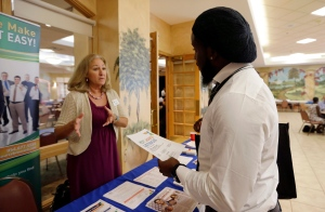 In this Oct. 6, 2015, photo, military veteran Mark Cannon, of Miami, right, talks with Cynthia Carcillo, a veterans outreach representative for Career Source Broward, about employment opportunities at a job fair for veterans, in Pembroke Pines, Fla. (AP / Lynne Sladky)