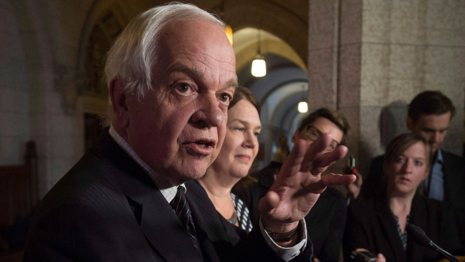 Jane Philpott, Minister of Health, listens as John McCallum, Minister of Immigration, Refugees and Citizenship responds to a question from the media following a meeting of the Ad Hoc Committee on Refugees on Parliament Hill in Ottawa, Friday Nov. 20, 2015. (Adrian Wyld / THE CANADIAN PRESS)