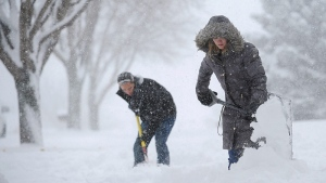 Hope Peterson, 22, and Alex Cutler, 24, both of Sioux Falls, shovel the sidewalk in front of Cutler's parents' house during the first snow of the season Friday, Nov. 20, 2015, in Sioux Falls, S.D. (Joe Ahlquist/The Argus Leader via AP)