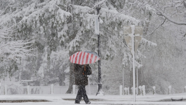 A pedestrian walks through the snow at campus of Andrews University in Berrien Springs, Mich. on Saturday, Nov. 21, 2015. (Don Campbell/The Herald-Palladium via AP)