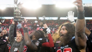 Ottawa Redblacks head coach Rick Campbell holds up the East Division trophy in Ottawa, on Nov. 22, 2015. (Adrian Wyld / THE CANADIAN PRESS)