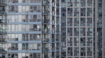 A man and woman, centre, stand on the balcony of a condo unit surrounded by other condominium towers in Yaletown in Vancouver, B.C., on Monday, Sept. 14, 2015. (THE CANADIAN PRESS/Darryl Dyck)