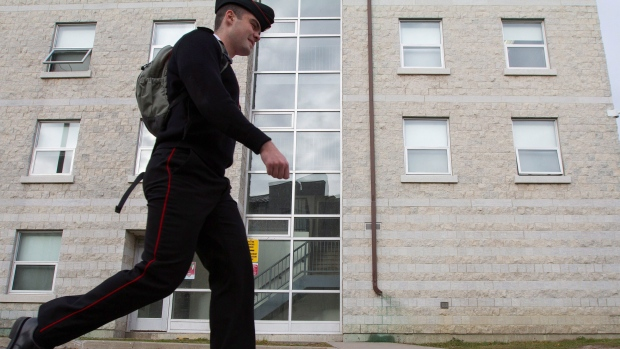 A military cadet walks by a barrack at Royal Military College of Canada in Kingston, Ont., on Monday Nov. 23, 2015. (Lars Hagberg / THE CANADIAN PRESS)