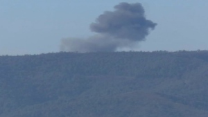 This frame grab from video shows smoke from a Russian warplane after crashing on a hill as seen from Hatay province, Turkey on Tuesday, Nov. 24, 2015. (Haberturk TV)