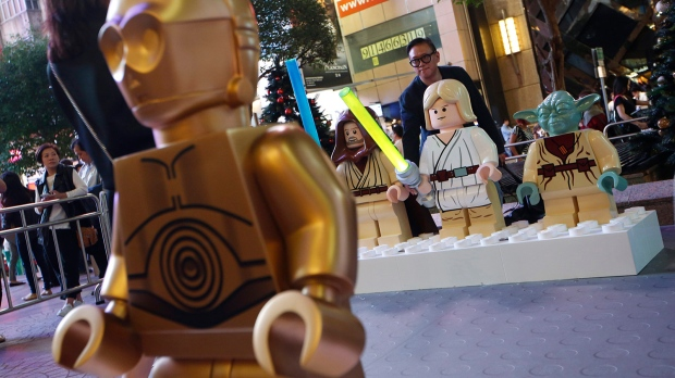 A fan poses for a photograph with the figures of Star Wars characters after the opening ceremony of the Lego Star Wars exhibition in Hong Kong, Tuesday, Nov. 24, 2015. (AP / Kin Cheung)