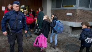 Children pass a police officer as they arrive for school in the center of Brussels on Wednesday, Nov. 25, 2015. (AP / Virginia Mayo)