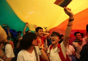 In this file photo, people celebrate underneath a large rainbow flag in Hanoi, Vietnam on Sunday Aug. 3, 2014. (AP/Hau Dinh)