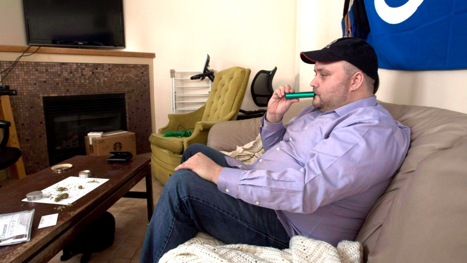 Clayton Goodwin inhales medicinal marijuana through a vaporizer at his apartment in Ottawa, Friday, March 20, 2015. (Adrian Wyld / THE CANADIAN PRESS)