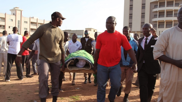 People carry a victim of the al Qaeda attack on the Radisson Blu hotel, in Bamako, Mali, on Wednesday, Nov. 25, 2015. (AP Photo/Baba Ahmed)