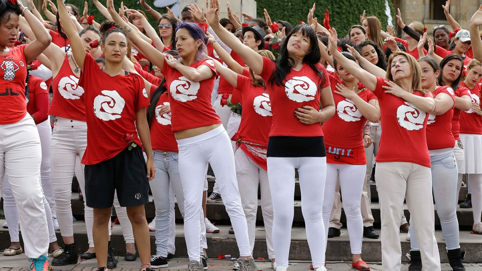 """Patricia Espitia who had acid thrown at her face by unknown assailants 7 years ago, front row second right, performs with a group of women during a demonstration against violence against women, at The II International Festival """"Not Even With a Rose Petal,"""" in Bogota, Colombia, Wednesday, Nov. 25, 2015. (AP / Fernando Vergara)"""