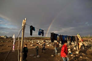 A rainbow stretches across the sky behind Syrian refugee children playing in an informal tented settlement near the Syrian border on the outskirts of Mafraq, Jordan on Oct. 29, 2015. (Muhammed Muheisen / AP Photo)