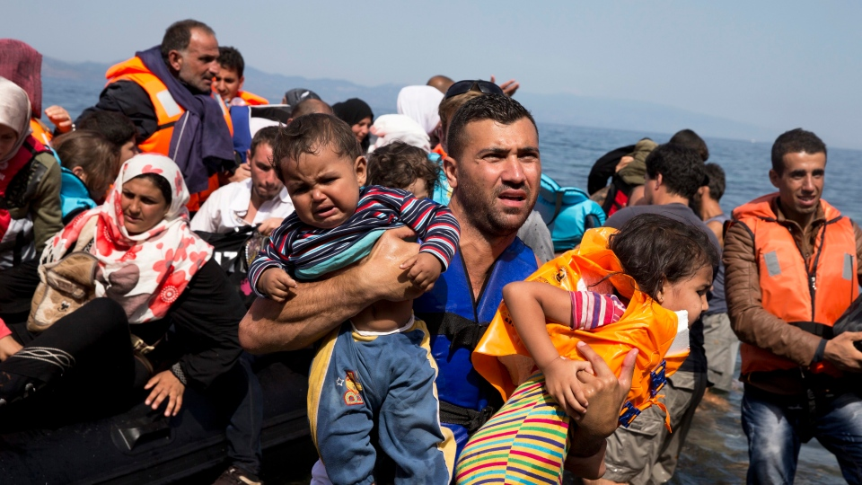 Syrian refugees arrive aboard a dinghy after crossing from Turkey to the island of Lesbos, Greece, on Sept. 10, 2015. (AP Photo/Petros Giannakouris)