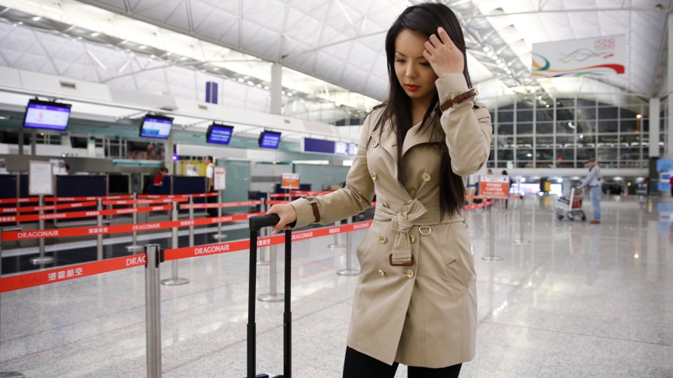 Canada's Miss World contestant Anastasia Lin walks away from the airline counter after she was denied entry to mainland China, at Hong Kong International Airport in Hong Kong, Thursday, Nov. 26, 2015. (AP / Kin Cheung)