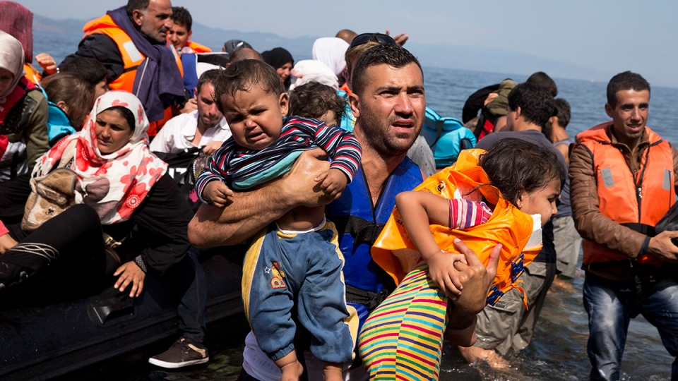 Syrian refugees arrive aboard a dinghy after crossing from Turkey to the island of Lesbos, Greece, in this Sept. 10, 2015. (AP / Petros Giannakouris)