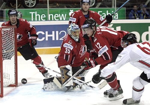 Switzerland's Romano Lemm, right, struggles for the puck with Canada's Eric Staal, centre, as Canada's goalkeeper Dwayne Roloson looks on during the IIHF World Hockey Championship quarterfinal in Moscow on Thursday, May 10, 2007. (AP / Sergey Ponomarev)