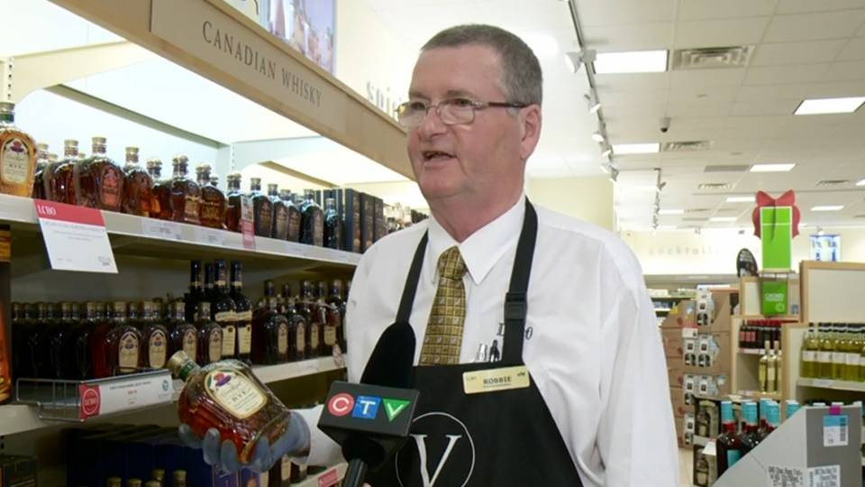 LCBO product consultant Robbie MacLead holds a bottle of Crown Royal rye at an Ottawa LCBO.