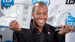 Ottawa Redblacks quarterback Henry Burris poses for photographs after winning the CFL's most outstanding player award and Tom Pate memorial award during the Canadian Football League awards in Winnipeg on Thursday November 26, 2015. (THE CANADIAN PRESS / Jonathan Hayward)