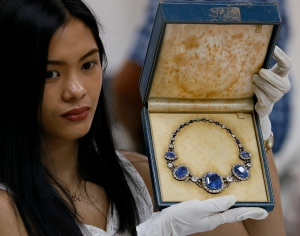 Katrina Camille Pena of the Presidential Commission on Good Government holds a set of jewelry from the so-called Hawaii Collection, one of three sets of the Marcos Jewelry Collection, during appraisal by Sotheby's at the Central Bank of the Philippines in Manila, Philippines on Friday, Nov. 27, 2015.  (AP / Bullit Marquez)