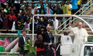 Pope Francis waves as he arrives for a meeting with youths at Kasarani Stadium, in Nairobi, Kenya, Friday, Nov. 27, 2015. Pope Francis is in Africa for a six-day visit that is taking him to Kenya, Uganda and the Central African Republic. (AP Photo/Sayyid Azim)