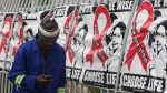 A man makes a call on a mobile phone as he passes past a World AIDS Day banners on the perimeter of an office building in Sandton, Johannesburg, South Africa, Monday, Dec. 1, 2014. (AP  /Denis Farrell)