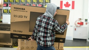 A customer carries a large TV to the checkout at a Best Buy store on Black Friday, shortly after the store's 6 a.m. opening on Friday, Nov. 27, 2015 in Ottawa. (Justin Tang / THE CANADIAN PRESS)