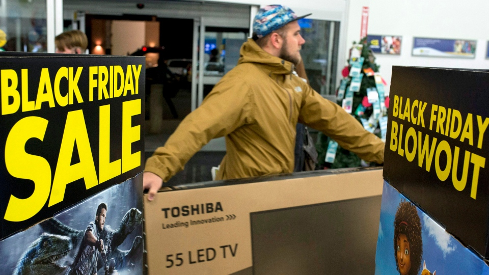 A customer carries a large TV to the checkout at a Best Buy store on Black Friday, shortly after the store's 6 a.m. opening in Ottawa on Friday, Nov. 27, 2015. (Justin Tang / THE CANADIAN PRESS)