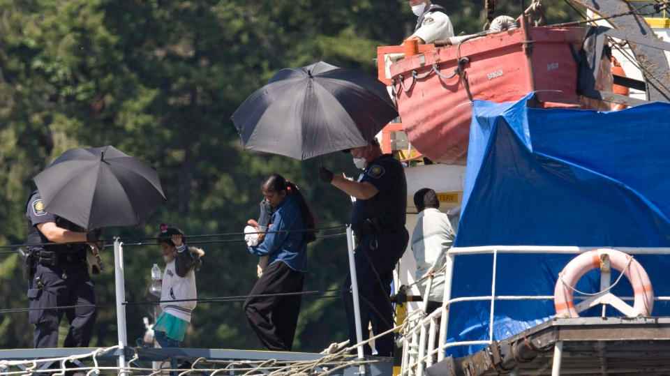 Migrants are escorted from the MV Sun Sea after it was escorted into CFB Esquimalt in Colwood, B.C. on Friday, Aug. 13, 2010. (Jonathan Hayward / THE CANADIAN PRESS)