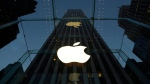 In this Wednesday, Nov. 20, 2013, file photo, the Apple logo is illuminated in the entrance to the Fifth Avenue Apple store, in New York. (AP Photo/Mark Lennihan)