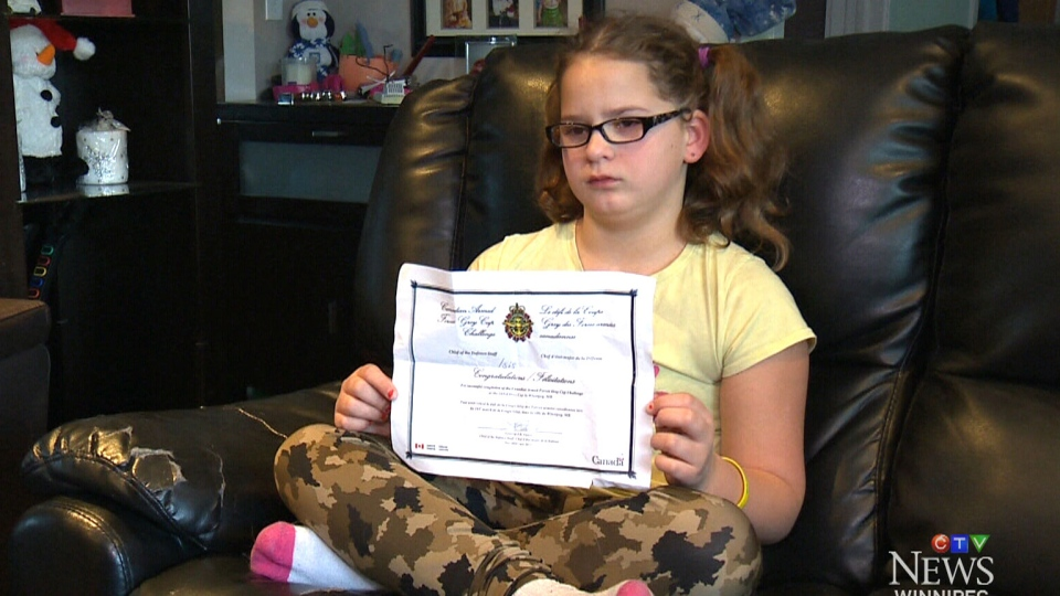 Isis Fernandes, a 9-year-old girl from Winnipeg, holds a certificate that she says a Canadian solider refused to sign during a school field trip in Winnipeg.