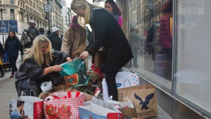 "Linda Meehan, left, and her daughters Nicole Flodin, second from left background, Genna Janenson, second from right and Emma Rumble, far right background, pack bags from their ""second round"" of shopping since arriving from their home in London, England, Friday, Nov. 27, 2015, in New York. (AP / Bebeto Matthews)"