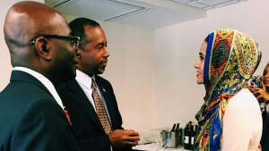In this photo taken on Oct. 9, 2015, provided by the Muslim Public Affairs Council, Rabiah Ahmed, Media and Communications Director of the Muslim Public Affairs Council, hand delivers a letter to Republican presidential candidate Ben Carson, inviting him to meet with members of the American Muslim community, at the National Press Club in Washington. (Khatol Aziz / Muslim Public Affairs Council via AP)