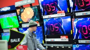 A holiday shopper browses the electronics section against a backdrop of televisions at a Target store, Friday, Nov. 27, 2015, in Newport, Ky. (AP / John Minchillo)