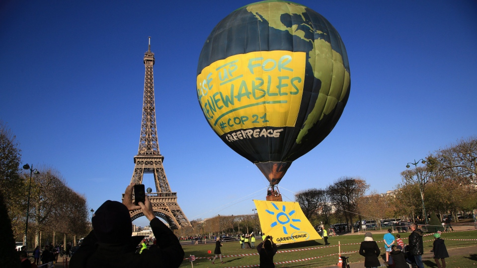 People take pictures of an hot air balloon of the environmental group Greenpeace, near the Eiffel Tower ahead of the 2015 Paris Climate Conference, in Paris, Saturday, Nov. 28, 2015. (AP Photo/Thibault Camus)