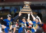 UBC Thunderbirds Terrell Davis, centre, raises the Vanier Cup trophy with quarterback Michael O'Connor, left, and Stavros Katsantonis, right, after winning against the Montreal Carabins, Saturday, November 28, 2015 in Quebec City. (Jacques Boissinot / THE CANADIAN PRESS)