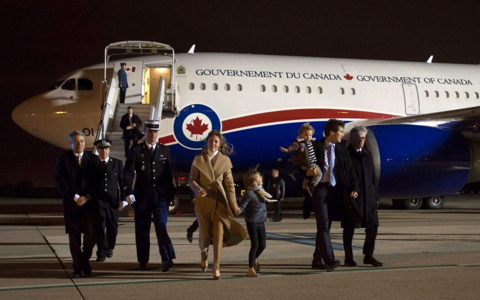 Canadian Prime Minister Justin Trudeau speaks with the Canadian Ambassador to France Lawrence Cannon as he walks across the tarmac with his wife Sophie Gregoire-Trudeau and their children Ella-Grace Trudeau and Hadrien Trudeau as they arrive at the airport Saturday, November 28, 2015 in Orly, France. (Adrian Wyld / THE CANADIAN PRESS)